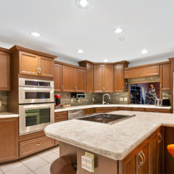 Light brown quartz kitchen countertops with traditional hardwood maple cabinets, induction stovetop, and stainless steel appliances, refaced kitchen cabinets in Columbus, OH by Lowe's National Refacing Systems.