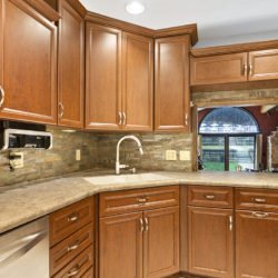 Maple hardwood kitchen cabinets with brown quartz countertops, stone tile backsplash, undermount white ceramic sink, and bar window, refaced kitchen cabinets in Columbus, OH by Lowe's National Refacing Systems.