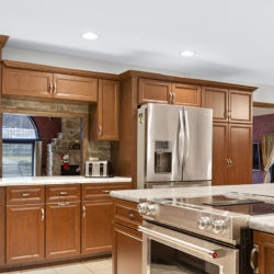 Traditional hardwood maple kitchen cabinets with maple crown molding, bar window, brown quartz countertops, and stainless steel appliances, refaced kitchen cabinets in Columbus, OH by Lowe's National Refacing Systems.
