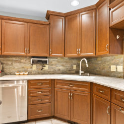 Traditional flat panel hardwood maple kitchen cabinets with undermount white ceramic sink, quartz countertops, and stone tile backsplash, refaced kitchen cabinets in Columbus, OH by Lowe's National Refacing Systems.