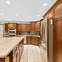 Hardwood maple flat panel kitchen cabinets and matching island with rubbed steel hardware and stainless steel appliances, refaced kitchen cabinets in Columbus, OH by Lowe's National Refacing Systems.