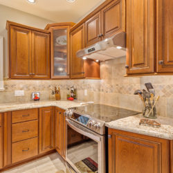 Traditional maple hardwood kitchen cabinets with island, undermount sink, and stainless steel appliances, refaced kitchen cabinets in Wilmington, DE by Lowe's National Refacing Systems.