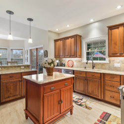 Hardwood maple kitchen cabinets and quartz countertop with island, refaced kitchen with open floor plan in Wilmington, DE by Lowe's National Refacing Systems.