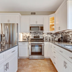 – Stainless steel appliances set on granite countertop, white contemporary refaced kitchen cabinets with glass front corner cabinet in Cleveland, OH by Lowe's National Refacing Systems.
