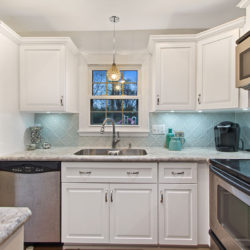 White traditional kitchen cabinets with crown molding, teardrop hanging light, undermount stainless steel sink, and rubbed steel hardware, refaced kitchen cabinets in Harrisburg, PA by Lowe's National Refacing Systems.
