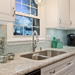 White traditional raised panel kitchen cabinet doors with rubbed steel hardware and undermount stainless steel sink, refaced kitchen cabinets in Harrisburg, PA by Lowe's National Refacing Systems.