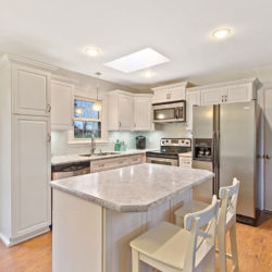 Traditional raised panel white kitchen cabinets with crown molding, grey marble countertops, undermount stainless steel sink and stainless steel appliances, refaced kitchen cabinets in Harrisburg, PA by Lowe's National Refacing Systems.