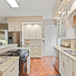 Traditional style white laminate kitchen cabinets with induction stovetop, undermount stainless steel sink, and white marble countertops, refaced kitchen cabinets in Philadelphia, PA by Lowe's National Refacing Systems.