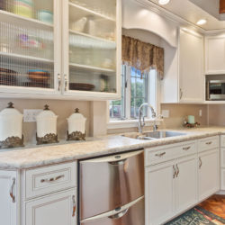 Stacked stainless steel dishwasher in white traditional refaced kitchen with textured glass front cabinet doors and undermount sink, refaced kitchen cabinets in Philadelphia, PA by Lowe's National Refacing Systems.