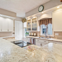 White marble kitchen countertops with traditional style white laminate cabinets and inlaid induction stovetop, refaced kitchen cabinets in Philadelphia, PA by Lowe's National Refacing Systems.