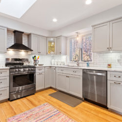 – Contemporary off-white kitchen cabinets with stainless steel refrigerator, glass droplights in open floor plan, refaced kitchen cabinets in Williamsport, PA by Lowe's National Refacing Systems.