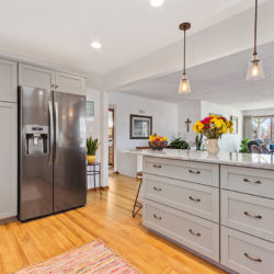Contemporary off-white kitchen cabinets with white marble countertops, stainless steel appliances, and wall-mounted range hood, refaced kitchen cabinets in Williamsport, PA by Lowe's National Refacing Systems.