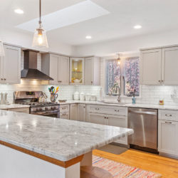 Contemporary inlaid style off-white kitchen cabinets with white marble countertops, glass front corner cabinets, and stainless steel appliances with wall mounted range hood, refaced kitchen cabinets in Williamsport, PA by Lowe's National Refacing Systems.