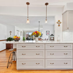 Off-white inlaid flat panel kitchen drawers with barstool and white marble countertops in open floor plan kitchen, refaced kitchen cabinets in Williamsport, PA by Lowe's National Refacing Systems.