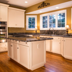 Antique White Kitchen with Laminate Recessed Panel Doors and Gray Countertops