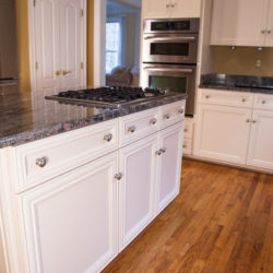 Cream White Laminate Island with Gas Cook-Top Stove and Stainless-Steel Appliances