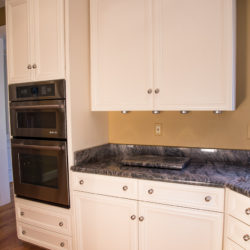Antique White Kitchen with Wall Over, Under Cabinet Lighting and Crown Molding