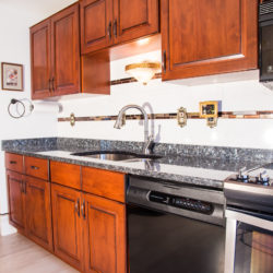 Dark Cherry Wood Kitchen with Gray Countertop and White Tile Backsplash and Decorative Tile Inlay