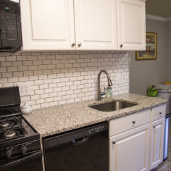 White Kitchen with Black Appliances, Gray  Countertop and Undermount Sink
